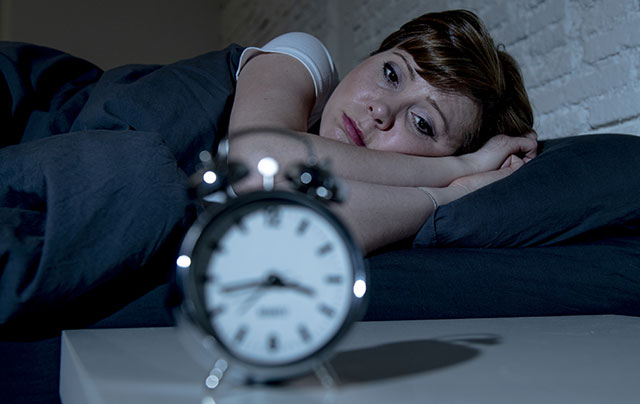 Sleep Deprivation - woman who can't sleep looking at a clock