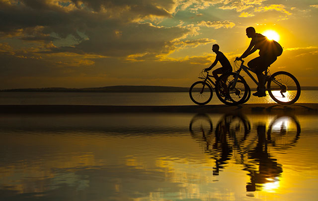 family riding bikes on beach