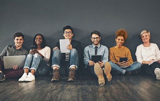 a group of millennials sitting with devices